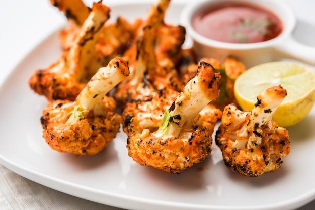 Tandoori gobi oder gerösteter blumenkohl tikka ist ein trockenes gericht, das durch rösten von blumenkohl im ofen, tandoor, hergestellt wird. es ist eine beliebte vorspeise aus indien. mit ketchup serviert. selektiver fokus