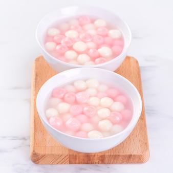 Tang yuan, tangyuan, köstliche rote und weiße reisknödelbällchen in einer kleinen schüssel. asiatisches traditionelles festliches essen für chinesisches wintersonnenwende-festival, nahaufnahme.