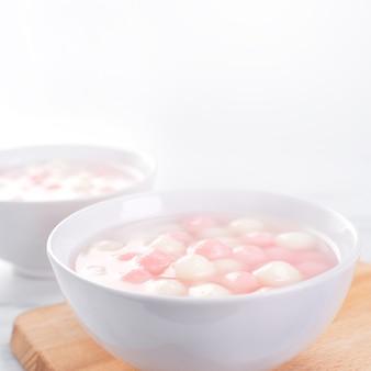Tang yuan, tangyuan, köstliche rote und weiße reisknödelbällchen in einer kleinen schüssel. asiatisches traditionelles festliches essen für das chinesische wintersonnenwende-festival, nahaufnahme.