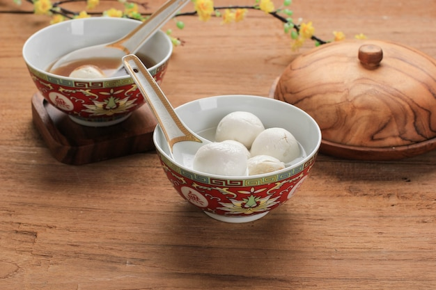 Tang yuan (wedang ronde), chinesische klebreis-knödelbällchen mit zuckeringwer oder palmzuckersirup auf rotem chinesen auf schwarzem hintergrund für wintersonnenwende-neujahrsfest-essen. platz kopieren