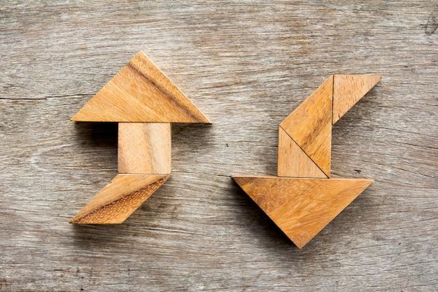 Tangram puzzle als zwei-wege-pfeil-form auf hölzernen hintergrund