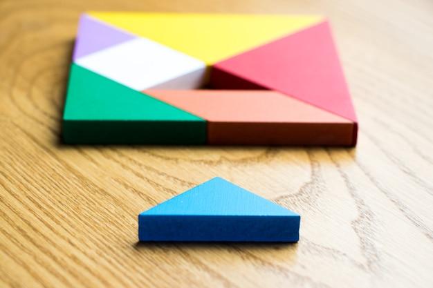 Tangram puzzle in quadratischer form, die auf holz hintergrund warten auf vollständigkeit