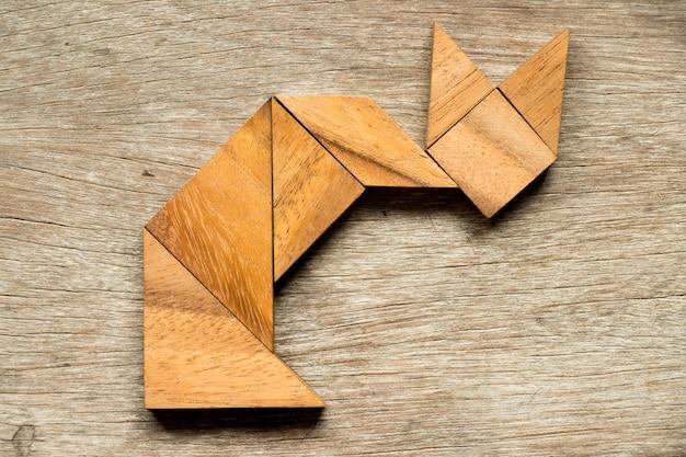 Tangramrätsel in sitzender form der katze auf hölzernem hintergrund