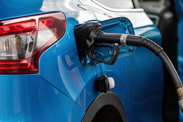 Tanken auto mit benzin an der tankstelle betanken und zapfsäule füllen kraftstoffdüse im kraftstofftank des autos