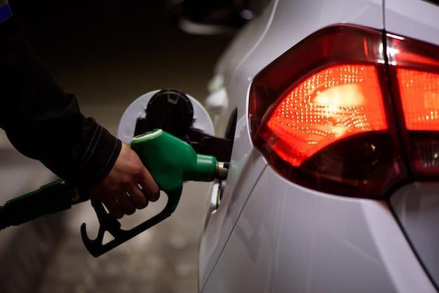 Tankstellenarbeiter in arbeitskleidung tankt luxusauto mit benzin, das die füllpistole an der station hält.