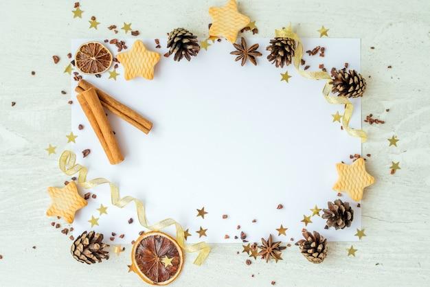 Tannen, kekse, zimt und goldene bänder auf weißem hintergrund. rahmen, der neujahrskarte zurücksetzt. weihnachtsferienkonzept. kopierraum, flach liegen