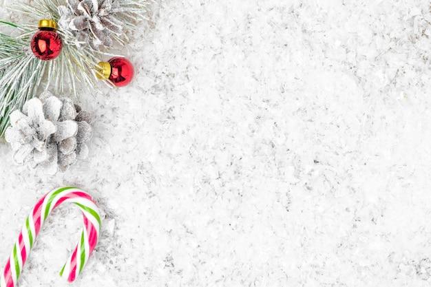 Tannen- oder fichtenzapfen zuckerstangenrohr rote kugeln auf dem schnee mit kopierraum