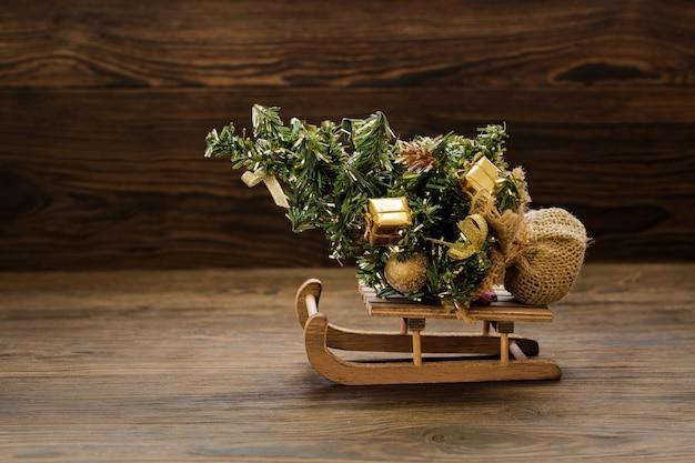 Tannenbaum auf schlitten mit weihnachtsschmuck