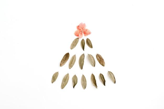 Tannenbaum aus getrockneten blättern und roter blütenknospe