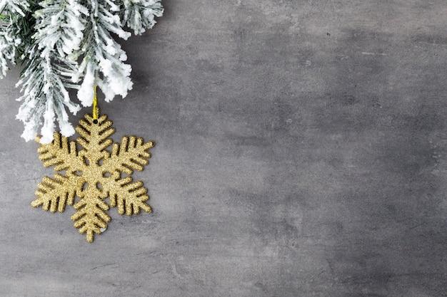 Tannenbaum bedeckt mit schnee auf grauem brett