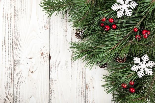 Tannenbaum mit weihnachtsschmuck auf dem rustikalen holzhintergrund