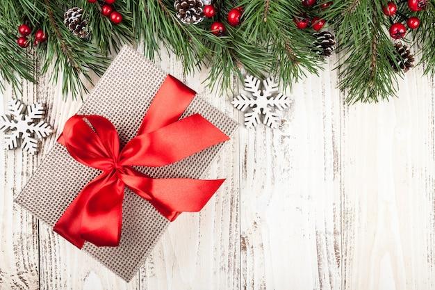 Tannenbaum mit weihnachtsschmuck und geschenkboxen auf vintage-holzhintergrund