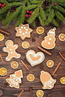 Tannenbaum und weihnachtslebkuchen auf dunkelbraunem holzhintergrund