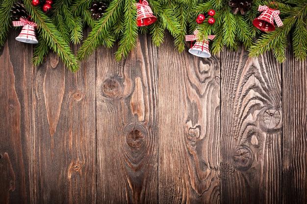 Tannenbaum verzierte glocken auf dunkelbraunem holzhintergrund