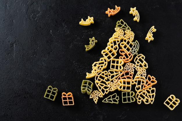 Tannenbaum von rohen weihnachtsnudeln auf einem schwarzen betontisch. kochkonzept. draufsicht mit kopierraum.