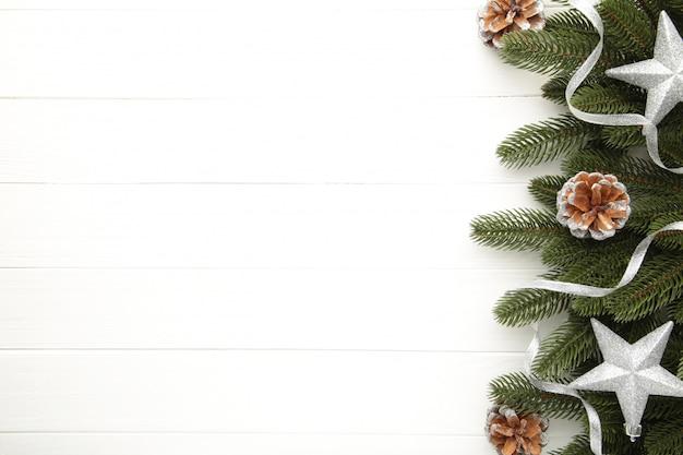 Tannenbaumaste mit silberner weihnachtsdekoration auf einem weißen hintergrund