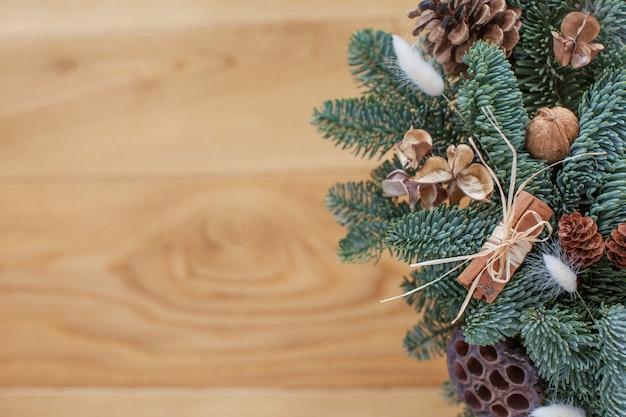 Tannenbaumaste mit weihnachtsdekorationen auf hölzernem hintergrund, copyspace