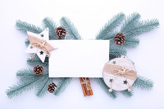 Tannenbaumaste mit weihnachtsspielwaren auf einem weißen hintergrund