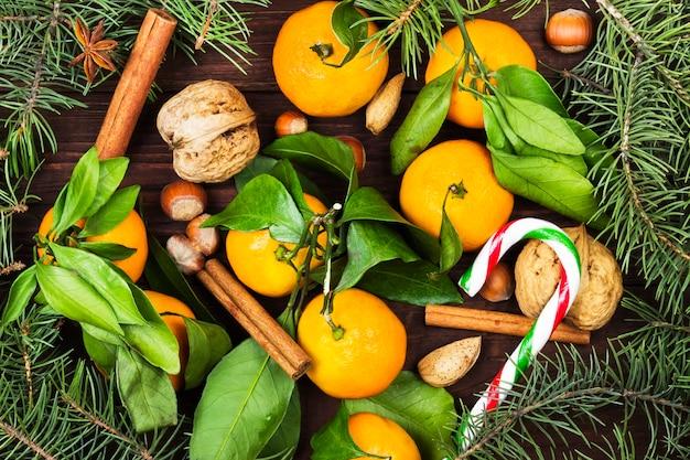 Tannenbaumaste, -nüsse, -zimt, -tangerinen und -süßigkeiten auf einer draufsicht der dunklen holzoberfläche