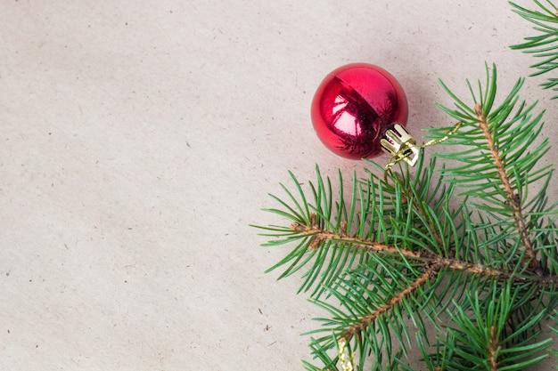 Tannenbaumaste verziert mit roten weihnachtsbällen als grenze an einem rustikalen feiertagshintergrundrahmen mit copyspace