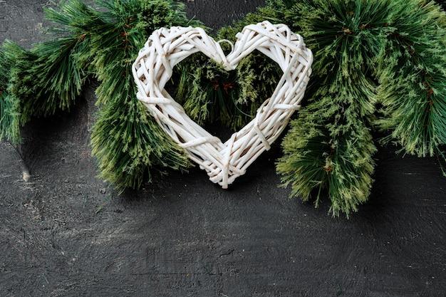Tannenbaumzweige mit holzherz auf schwarzem, weihnachtshintergrund