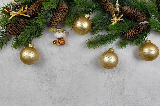 Tannenbaumzweige und goldene weihnachtsdekorationen auf grauem steinhintergrund