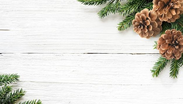 Tannenbaumzweige und kiefernkegel auf weißem hölzernem rustikalem hintergrund. weihnachtskomposition. platz kopieren