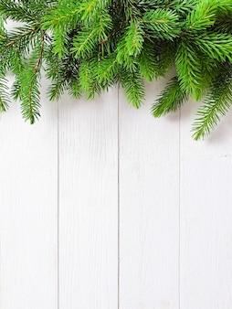 Tannengrenze auf weißem hölzernem hintergrund. draufsicht des weihnachtsrahmens