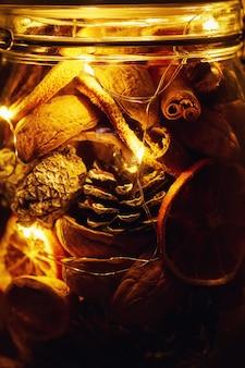 Tannenzapfen, getrocknete orangen und lichterketten im glas