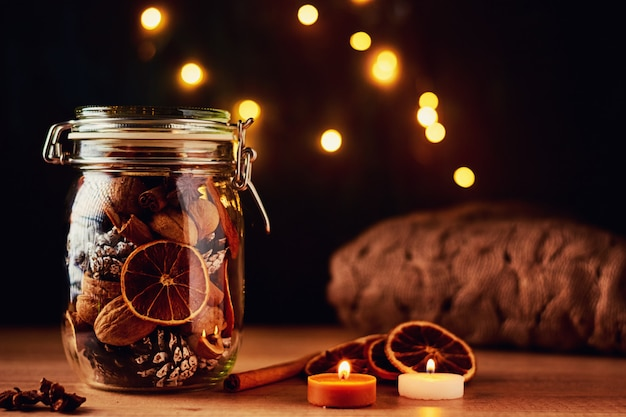 Tannenzapfen im glas und lichterketten auf einem dunklen hintergrund. festliche dekorationen