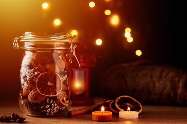 Tannenzapfen im glas und lichterketten auf einem dunklen hintergrund.
