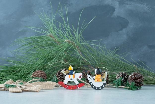 Tannenzapfen mit kleinen festlichen weihnachtsspielzeugen auf marmorhintergrund. hochwertiges foto