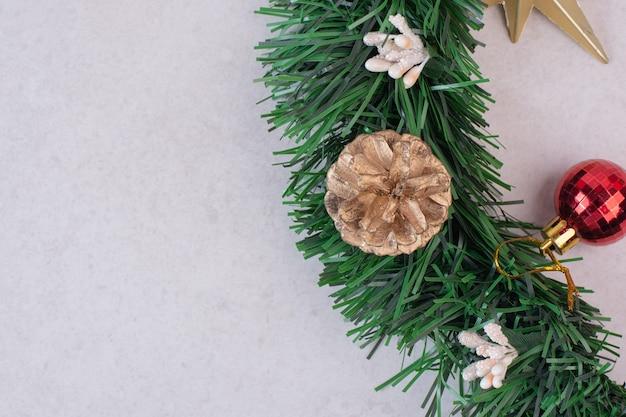 Tannenzapfen mit weihnachtskugel auf weißer oberfläche