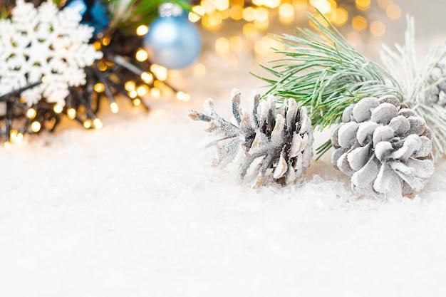 Tannenzapfen und fichtenzweig mit schnee bedeckt