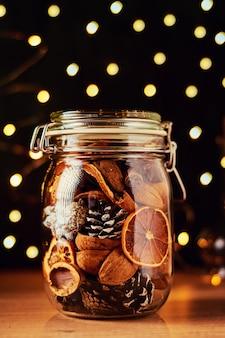 Tannenzapfen und getrocknete orangen im glasgefäß und in lichterketten bokeh auf einem dunklen hintergrund
