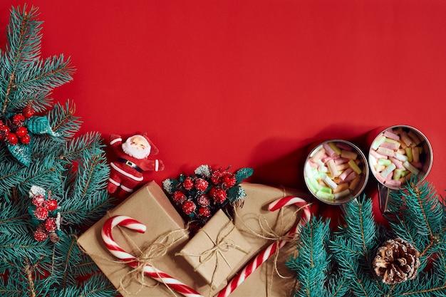 Tannenzweig, geschenkbox und zwei tassen kakao mit marshmallows auf rotem grund. ansicht von oben. flach liegen. platz kopieren. stillleben. weihnachten und silvester