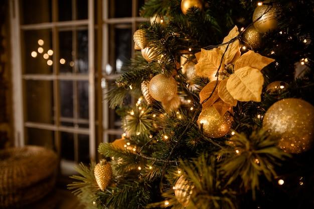 Tannenzweig mit bällen und festlichen lichtern auf dem weihnachtshintergrund mit scheinen
