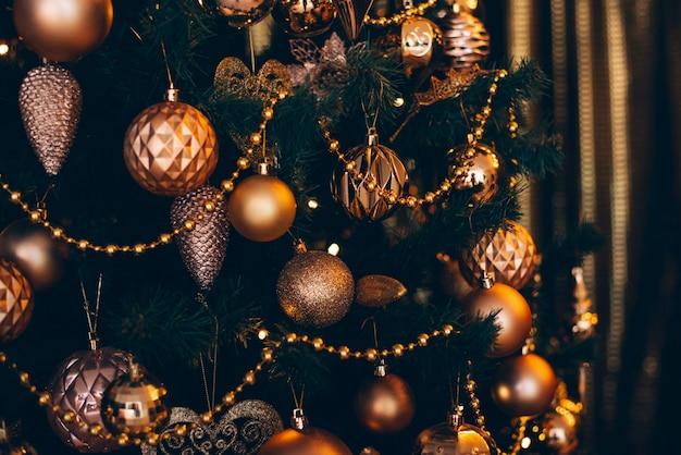 Tannenzweig mit goldenen bällen und festlichen lichtern auf dem dunklen hintergrund mit scheinen.