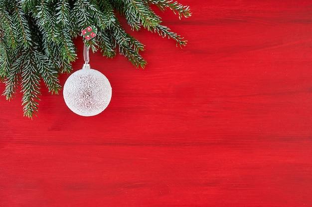 Tannenzweig mit weißer weihnachtskugel auf einer roten oberfläche