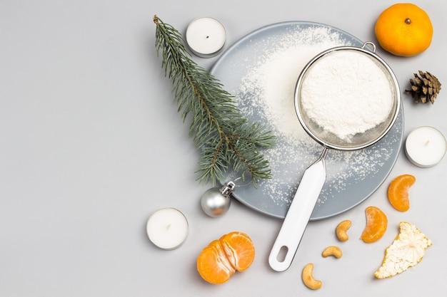 Tannenzweig, sieb mit mehl auf grauem teller, mandarine und mandarinenscheiben