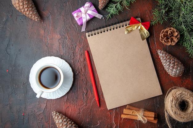 Tannenzweige dekoration zubehör nadelbaum zapfen geschenk und notizbuch eine tasse schwarzen tee auf dunklem hintergrund