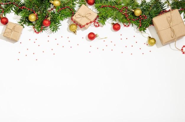Tannenzweige, geschenkboxen, weihnachtskugeln in roter und goldener farbe zur dekoration, rote perlen zur dekoration auf weißem hintergrund. kopierraum, flach liegen. sicht von oben