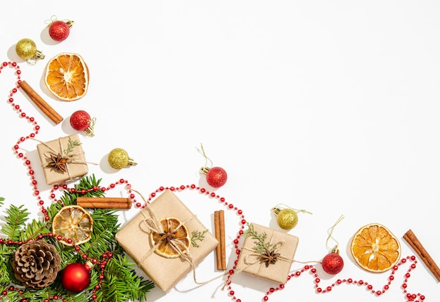 Tannenzweige, geschenkboxen, weihnachtskugeln, rote perlen zur dekoration, tannenzapfen, zimt, trockene orangenscheiben auf weißem hintergrund. kopierraum, flach liegen. sicht von oben