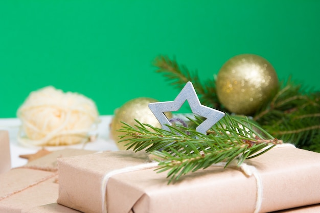 Tannenzweige, glänzende goldkugeln für den weihnachtsbaum und eine geschenkbox, die in kraftpapier eingewickelt und mit einem holzstern auf grünem hintergrund verziert ist, öko-weihnachtskonzept