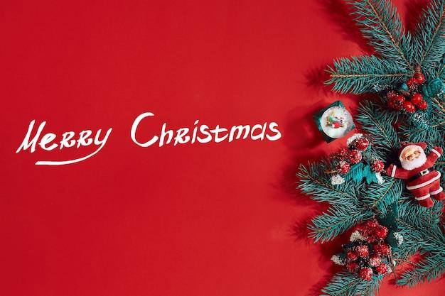 Tannenzweige grenzen auf rotem hintergrund, gut für weihnachtshintergrund. ansicht von oben. flach liegen. platz kopieren. stillleben. die inschrift - frohe weihnachten und neues jahr