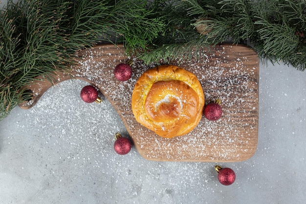 Tannenzweige, holzbrett, weihnachtsbaumspielzeug und ein kleines brötchen auf marmoroberfläche