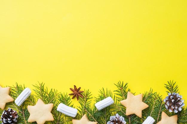Tannenzweige, kekse und marshmallows auf gelb