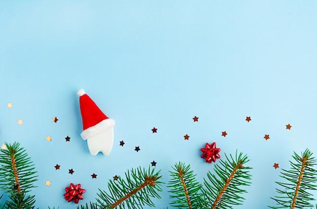 Tannenzweige, kreativer spielzeugzahn in roter weihnachtsmütze und sternen, flach gelegen