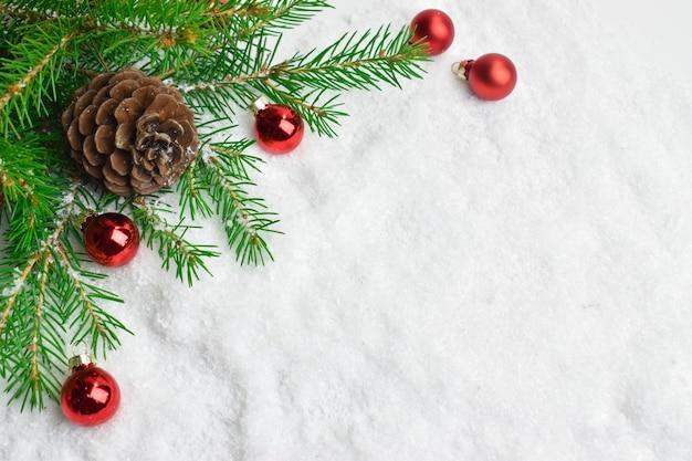 Tannenzweige mit roten weihnachtskugeln und zapfen.