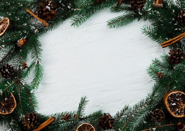 Tannenzweige mit schnee auf weißem brett